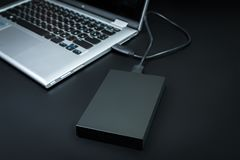 Ένας εξωτερικός σκληρός δίσκος σύνδεσε με το lap-top με ένα καλώδιο usb σε ένα μαύρο υπόβαθρο Στοκ εικόνα με δικαίωμα ελεύθερης χρήσης