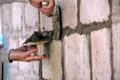 Ένας επαγγελματίας χτίζει ένα σπίτι Εργασία με το κονίαμα στοκ εικόνες