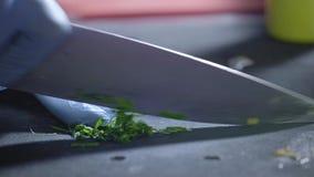 Ένας επαγγελματικός μάγειρας στην κουζίνα κόβει μια δέσμη του μαϊντανού με ένα μεγάλο μαχαίρι Κατάλληλα διατροφή και wellness προ απόθεμα βίντεο