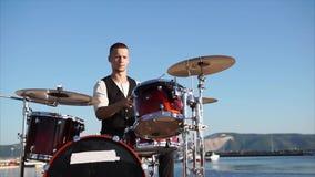 Ένας επαγγελματικός μουσικός παίζει ένα μουσικό όργανο αποκαλούμενο τύμπανο που τίθεται με τα πιάτα απόθεμα βίντεο