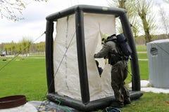 Ένας επαγγελματικός πυροσβέστης σε ένα μαύρο ειδικό αλεξίπυρο κοστούμι προετοιμάζεται να συγκεντρώσει μια άσπρη σκηνή οξυγόνου γι στοκ εικόνες