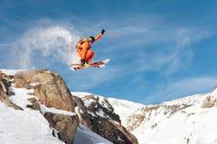 Ένας επαγγελματικός σκιέρ κάνει μια άλμα-πτώση από έναν υψηλό απότομο βράχο ενάντια σε έναν μπλε ουρανό αφήνοντας ένα ίχνος της σ Στοκ Φωτογραφίες
