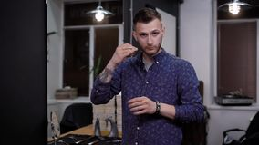 Ένας επαγγελματικός στιλίστας τρίχας που εργάζεται στο barbershop κρατά το ψαλίδι για την τέμνουσα τρίχα, ένα άτομο στρίβει ένα α φιλμ μικρού μήκους