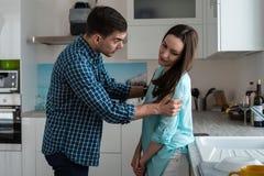 Ένας επιθετικός νεαρός άνδρας κρατά μια γυναίκα από τους ώμους και τις κραυγές, προβλήματα στην οικογένεια, εσωτερικές φιλονικίες Στοκ Εικόνες
