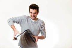 Ένας επιθετικός νεαρός άνδρας προσπαθεί να σπάσει το lap-top του ο άλλος τρόπος γύρω στοκ εικόνα με δικαίωμα ελεύθερης χρήσης