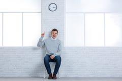 Ένας επιθετικός τύπος, κάθεται σε μια καρέκλα και κραυγάζει θυμωμένα την παρουσίαση έναν αντίχειρας-επάνω Στοκ φωτογραφία με δικαίωμα ελεύθερης χρήσης