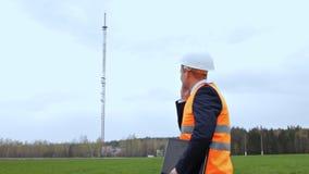 Ένας επιθεωρητής ατόμων κρατά ένα lap-top στο χέρι του και μιλά στο τηλέφωνο, σε ένα κλίμα ενός τηλεφωνικού πύργου απόθεμα βίντεο