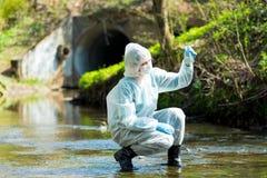 ένας επιστήμονας με έναν σωλήνα δοκιμής παίρνει ένα δείγμα του νερού στοκ εικόνες