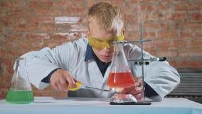 Ένας επιστήμονας πραγματοποιεί ένα πείραμα και τα φω'τα χεριών του επάνω φιλμ μικρού μήκους