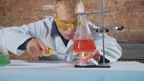 Ένας επιστήμονας πραγματοποιεί ένα πείραμα και τα φω'τα χεριών του επάνω απόθεμα βίντεο