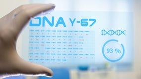 Ένας επιστήμονας χρησιμοποιεί μια φουτουριστική ταμπλέτα για να πραγματοποιήσει την έρευνα για το DNA ελεύθερη απεικόνιση δικαιώματος