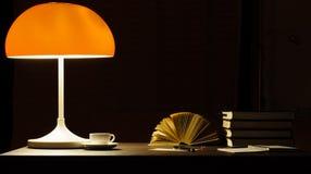 Ένας επιτραπέζιος λαμπτήρας ανάβει επάνω τα βιβλία στο γραφείο στοκ εικόνες