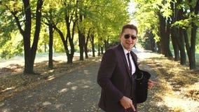 Ένας επιτυχής επιχειρηματίας σε ένα κοστούμι και τα γυαλιά ηλίου που χορεύουν στο πάρκο φθινοπώρου φιλμ μικρού μήκους