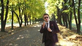 Ένας επιτυχής επιχειρηματίας σε ένα κοστούμι και τα γυαλιά ηλίου που χορεύουν στο πάρκο φθινοπώρου απόθεμα βίντεο