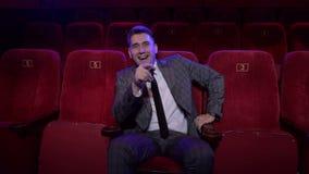 Ένας επιτυχής επιχειρηματίας σε ένα κοστούμι σε μια κινηματογραφική αίθουσα και τα ρολόγια ένας αστείος κινηματογράφος φιλμ μικρού μήκους