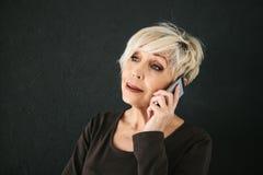 Ένας επιτυχής θετικός ηλικιωμένος θηλυκός σύμβουλος διαπραγματεύεται ένα τηλέφωνο κυττάρων Επικοινωνία μεταξύ της χρησιμοποίησης  στοκ φωτογραφία