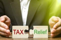 Ένας επιχειρηματίας βάζει δύο γρίφους με το φόρο και την ανακούφιση λέξεων Η έννοια της μείωσης του δανειακού βάρους στην επιχείρ στοκ φωτογραφία με δικαίωμα ελεύθερης χρήσης