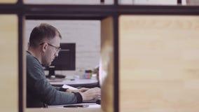 Ένας επιχειρηματίας κάθεται στο γραφείο γραφείων του, που λειτουργεί με προσήλωση στον υπολογιστή Οι κινήσεις καμερών ομαλά προς  απόθεμα βίντεο