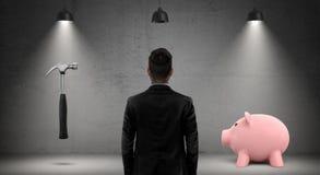 Ένας επιχειρηματίας κατά μια πίσω άποψη κοιτάζει μεταξύ ενός σφυριού και μιας piggy τράπεζας που στέκονται κάτω από τους βιομηχαν στοκ φωτογραφίες με δικαίωμα ελεύθερης χρήσης