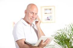 Ένας επιχειρηματίας με ένα lap-top και ένα τηλέφωνο Στοκ εικόνες με δικαίωμα ελεύθερης χρήσης