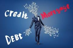 Ένας επιχειρηματίας με τα χρήματα που πετούν έξω από το περιλαίμιο και τα όπλα του, και η υποθήκη λέξεων, η πίστωση και το χρέος  στοκ εικόνες