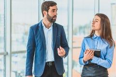 Ένας επιχειρηματίας με το γραμματέα του είναι ντυμένος στα επιχειρησιακά ενδύματα Κατά τη διάρκεια αυτού μιλούν στοκ εικόνες με δικαίωμα ελεύθερης χρήσης