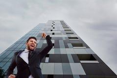 Ένας επιχειρηματίας που κραυγάζει αυξάνοντας το χέρι του επάνω ενάντια σε μια επιχείρηση β Στοκ φωτογραφία με δικαίωμα ελεύθερης χρήσης