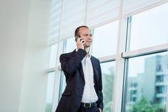 Ένας επιχειρηματίας που μιλά σε ένα κινητό τηλέφωνο, επιχειρηματίας που μιλά στο τ Στοκ Εικόνα