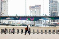 Ένας επιχειρηματίας που περπατά σε Reuters Plaza στο Canary Wharf Στοκ Εικόνες