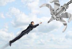 Ένας επιχειρηματίας που πετά μέσω των σύννεφων έτοιμων να αντιμετωπίσουν ένα μεταλλικό ρομποτικό χέρι Στοκ φωτογραφία με δικαίωμα ελεύθερης χρήσης
