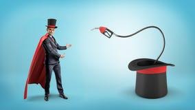 Ένας επιχειρηματίας που φορά ένα κόκκινο ακρωτήριο και ένα μεγάλο καπέλο θαυματοποιών ` s παρουσιάζει ακροφύσιο καυσίμων μέσα σε  Στοκ φωτογραφίες με δικαίωμα ελεύθερης χρήσης