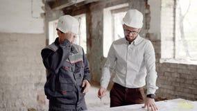 Ένας επιχειρηματίας σε ένα κράνος στο κεφάλι του και μια επαγγελματική οικοδόμηση που συζητά τα σχεδιαγράμματα του κτηρίου, τα άτ απόθεμα βίντεο