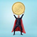 Ένας επιχειρηματίας σε ένα κόκκινο ρέοντας ακρωτήριο και μια μάσκα που κρατούν ένα τεράστιο χρυσό νόμισμα σε δικοί του παραδίδει  Στοκ εικόνες με δικαίωμα ελεύθερης χρήσης