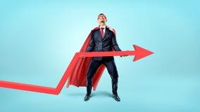 Ένας επιχειρηματίας σε ένα κόκκινο ρέοντας ακρωτήριο που προσπαθεί να ανυψώσει ένα μεγάλο κόκκινο βέλος προς τα πάνω στο μπλε υπό στοκ φωτογραφίες