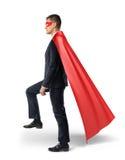 Ένας επιχειρηματίας σε ένα ρέοντας κόκκινο ακρωτήριο που περπατεί σε μια αόρατη σκάλα μπροστινή κίνηση στοκ φωτογραφίες με δικαίωμα ελεύθερης χρήσης