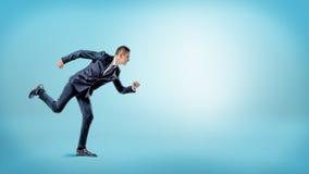 Ένας επιχειρηματίας σε μια θέση δρομέων έτοιμη να αρχίσει στο μπλε υπόβαθρο επιχείρηση νέα Στοκ φωτογραφία με δικαίωμα ελεύθερης χρήσης