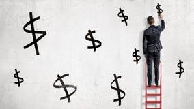 Ένας επιχειρηματίας στέκεται σε ένα κόκκινο stepladder και επισύρει την προσοχή τα μαύρα σημάδια δολαρίων σε έναν άσπρο τοίχο Στοκ εικόνα με δικαίωμα ελεύθερης χρήσης