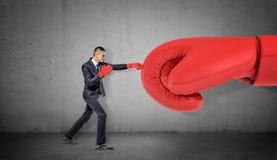 Ένας επιχειρηματίας στα εγκιβωτίζοντας γάντια στο συγκεκριμένο υπόβαθρο τρυπά ένα γιγαντιαίο κόκκινο γάντι με διατρητική μηχανή Στοκ Εικόνες