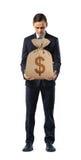 Ένας επιχειρηματίας στο άσπρο υπόβαθρο που κρατά έναν σάκο με ένα σημάδι δολαρίων τύπωσε σε το Στοκ Εικόνα