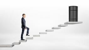 Ένας επιχειρηματίας στο άσπρο υπόβαθρο που περπατά επάνω τα σκαλοπάτια τσιμεντένιων ογκόλιθων όπου ένα μαύρο βαρέλι πετρελαίου στ στοκ εικόνες με δικαίωμα ελεύθερης χρήσης