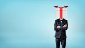 Ένας επιχειρηματίας στο μπλε υπόβαθρο που στέκεται κατά την μπροστινή άποψη με τα χέρια του διέσχισε και ένα κιβώτιο δώρων αντί τ Στοκ εικόνες με δικαίωμα ελεύθερης χρήσης