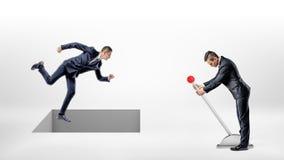 Ένας επιχειρηματίας τρέχει στο άσπρο έδαφος ενώ μια τετραγωνική τρύπα που ελέγχεται από ένα άτομο σε έναν μοχλό ανοίγει δεξιά κάτ Στοκ Φωτογραφία