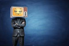Ένας επιχειρηματίας φορά μια αναδρομική TV στο κεφάλι του και μεταδίδει ραδιοφωνικά ένα κίτρινο απογοητευμένο emoji Στοκ Φωτογραφία