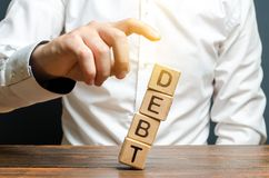 Ένας επιχειρηματίας ωθεί κάτω έναν πύργο των κύβων με το χρέος λέξης έννοια της οικονομικής βοήθειας, αναδόμηση δανείου Οικονομικ στοκ εικόνες