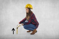 Ένας εργάτης οικοδομών μετρά κάτι μικρό, συμβολικός Grow στοκ φωτογραφίες