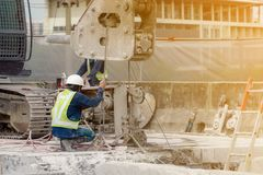 Ένας εργάτης οικοδομών στο πράσινο γιλέκο και το άσπρο κράνος εργάζεται με τη μηχανή στην περιοχή κατασκευής στοκ φωτογραφίες με δικαίωμα ελεύθερης χρήσης