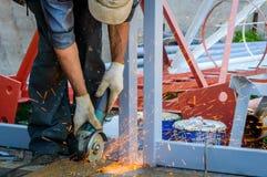 Ένας εργάτης οικοδομών βιομηχανίας χρησιμοποιώντας έναν μύλο γωνίας για την περικοπή του metall και παράγοντας πολλούς σπινθήρες Στοκ Εικόνες