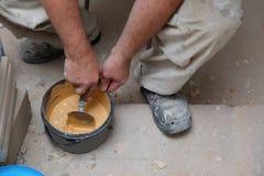 Ένας εργαζόμενος αναμιγνύει το χέρι-ξηρό ρευστοκονίαμα τσιμέντου στο χρώμα μαρέγκας με το νερό χρησιμοποιώντας ένα trowel Για να  στοκ εικόνα με δικαίωμα ελεύθερης χρήσης