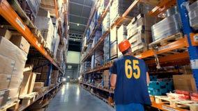 Ένας εργαζόμενος αποθηκών εμπορευμάτων με μια περιοχή αποκομμάτων κατά την πίσω άποψη φιλμ μικρού μήκους