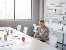 Ένας εργαζόμενος γραφείων στηρίζεται στο γραφείο του Στοκ εικόνα με δικαίωμα ελεύθερης χρήσης